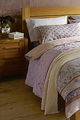 Wooden bed with patterned bedding