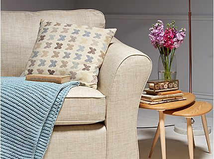 A sofa, cushion, throw and nest of side tables