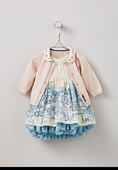Pink cardigan and white and blue city print frilly dress